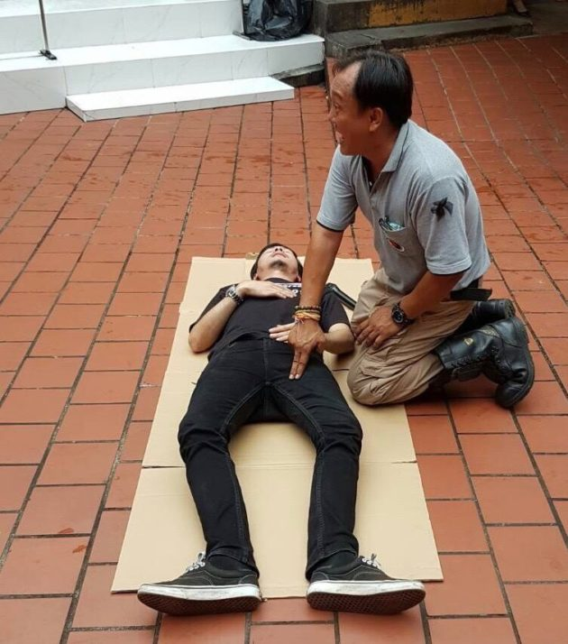 An instructor demonstrates primary first aid techniques.