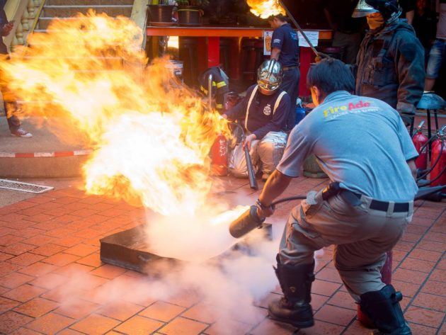 An instructor demonstrates fire extinguisher use.