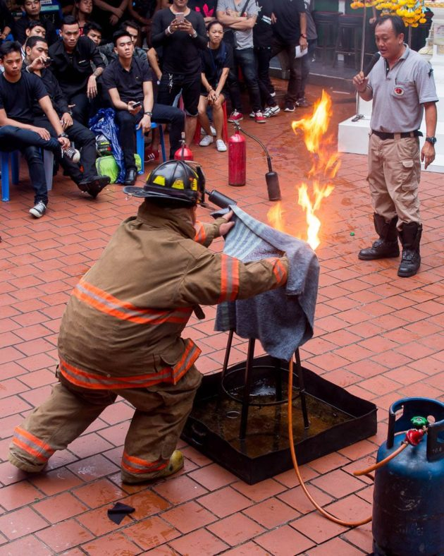 A firefighter demonstrates how to smother a grease fire.